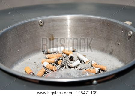 close-up of the cigarette butt smashed in a black ashtray