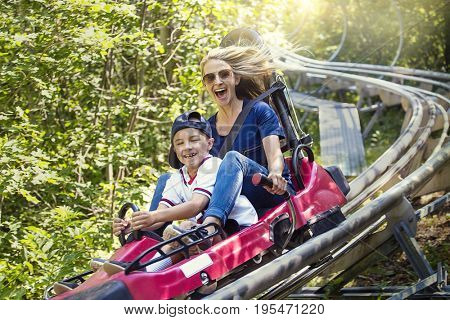 Smiling women and her boy riding downhill together on an outdoor roller coaster on a warm summer day. She has a fun expression as they enjoy a thrilling ride on a red amusement park ride
