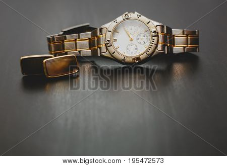 Stylish male watch with cuff in wooden background