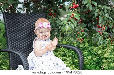 Little girl sits on a chair against the background of a cherry tree and tall grass.