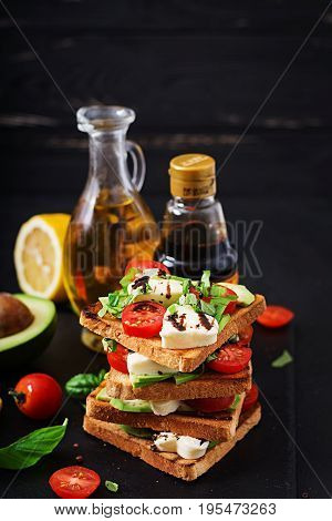 Sandwich Toasts With Tomatoes, Mozzarella, Avocado And Basil With Balsamic Vinegar.