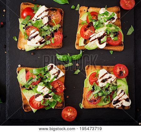 Sandwich Toasts With Tomatoes, Mozzarella, Avocado And Basil With Balsamic Vinegar. Flat Lay. Top Vi