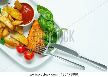 Baked potato wedges with cheese and herbs and tomato sauce on white plate - homemade organic vegetable vegan vegetarian potato wedges snack food meal.