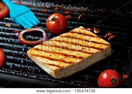 The process of cooking frying pieces of Tofu on a special grill pan. Vegetarian dishes. Soy Tofu Grilled. Soft focus. Close up