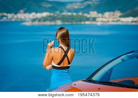 Beautiful young woman with long hair smoking and standing near orange cabriolet at the Mediterranean sea coast
