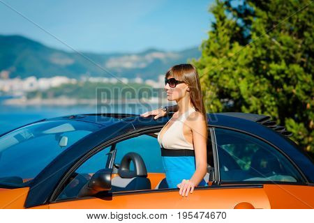 Beautiful Young Woman With Long Hair With Orange Cabriolet At The Mediterranean Sea Coast