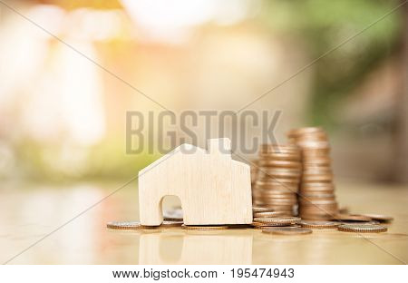 wooden house model and step of coins stacks nature background money saving and investment or family planning concept over sun flare silhouette tone.