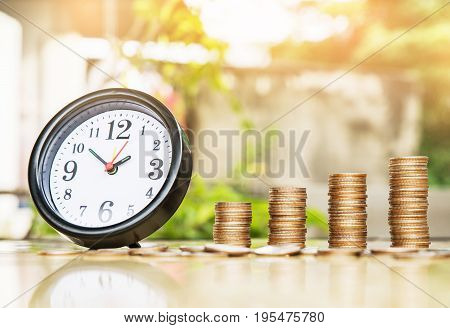 Clock alarm and step of coins stacks nature background money saving and investment or family planning concept over sun flare silhouette tone.
