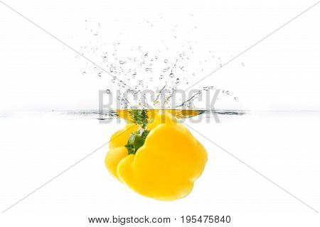 Yellow bellpepper dropped into the water with water splash on a white background