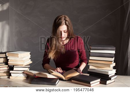 girl reading a book in the library is preparing for the exam 1