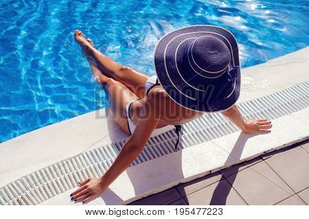 Beautiful tanned young woman with perfect body wearing white bikini and hat. outdoor shot. copy space.