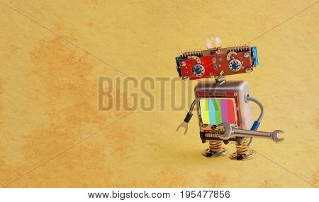 Repair service robot handyman master with hand wrench. Creative design smiley cyber toy character, screen with no signal TV test multicolor pattern background. Vintage paper background copy space.
