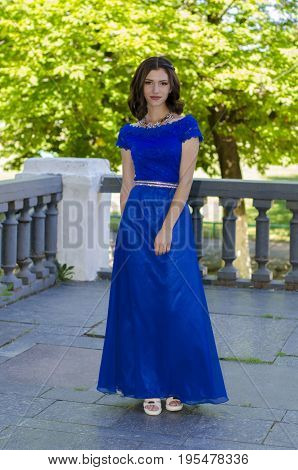 Beautiful girl in a blue dress posing against a background of massive handrails.