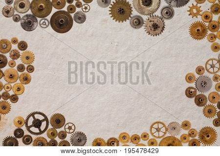 Cog gear wheel mechanic machinery ornament on vintage textured paper background. Retro technology parts closeup, aged clockwork details