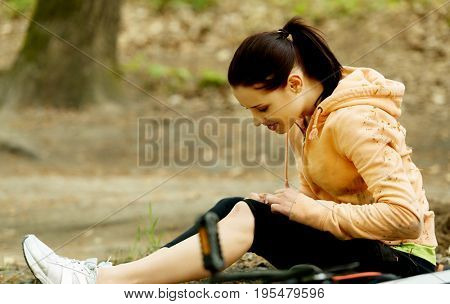 Young female bicyclist with hurt leg