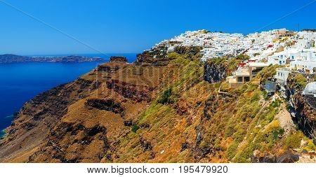Hotels of Fira town on the slopes of a volcanic mountain overlooking the sea and Caldera of Santorini, Greece.