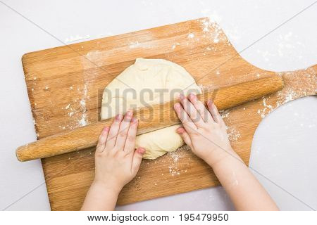 Children's hands rolled dough with a rolling pin on the wooden board