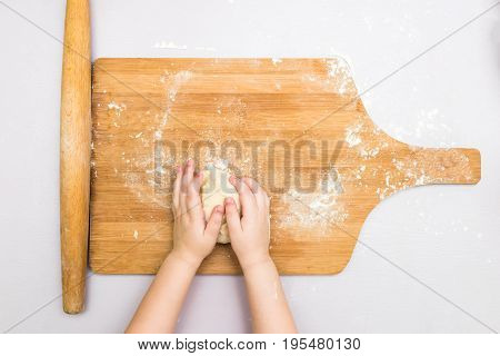 Top view children's hands make a dough on the wooden board