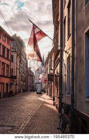 Latvian flag on the street illuminated by the rays of the sun