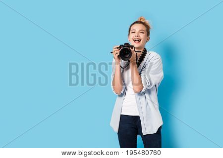 Young Blonde Photographer Is Enjoying Her Work. Model Isolated On A Blue Background With Copy Space