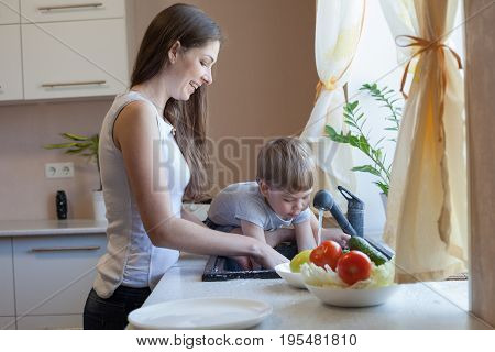 mom cleans the vegetables in the kitchen boy it interferes
