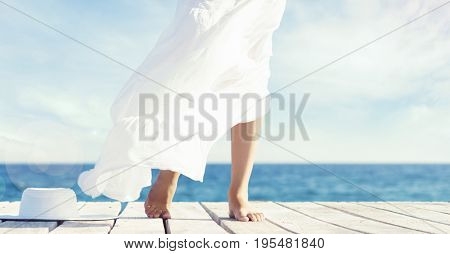 Beautiful and healthy feet of a young girl in white dress on a wooden pier. Sea and sky background. Vacation, resort and traveling concept.