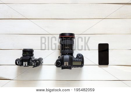 Evolving Technologies Concept. Vintage Film Camera Digital Camera Smartphone On White Wooden Background. Top View