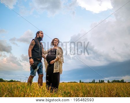 man in a black cloth and a pregnant woman in a black long dress and dreadlocks embrace and are kept in hand, against the background of yellow grass field, nature, autumn or summer. love story. Informal people with tattoo and piersing. Young family.