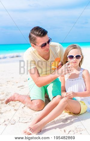 Young father applying sun cream to daughter nose on the beach