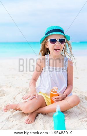 Little adorable girl applying sun cream during beach vacation
