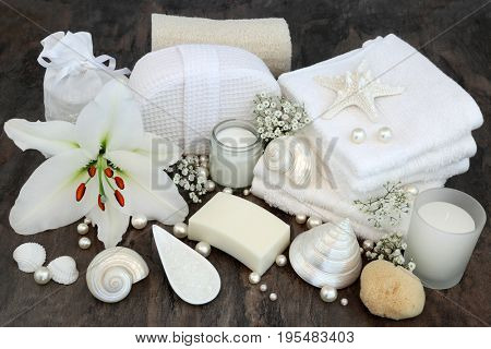 White lily flower with cleansing beauty treatment accessories including natural loofah, moisturizing cream, soap, flannels, salt, natural sponge with shells and pearls.