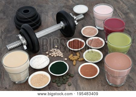 Weight training equipment for body builders with dumbbell weights, dietary food supplements and vitamins with health drink selection.