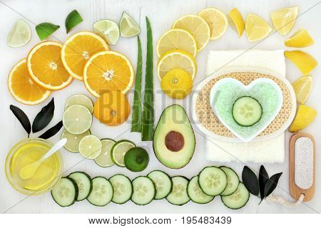 Ingredients for body and skin care beauty treatment with cucumber, avocado, aloe vera and citrus fruit and bathroom accessories on distressed white wood background.