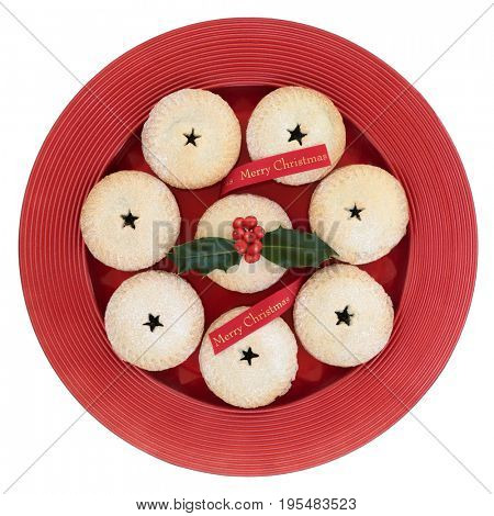 Mince pies with holly and red merry christmas ribbon on a plate isolated on white background.