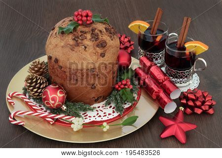 Christmas chocolate panettone cake with mulled wine, bauble decorations, candy canes, holly, mistletoe, fir, gold pine cones on oak background.