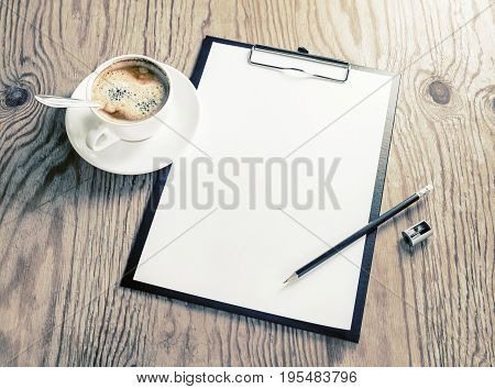 Clipboard with blank letterhead coffee cup pencil and sharpener on wood table background. Responsive design template.