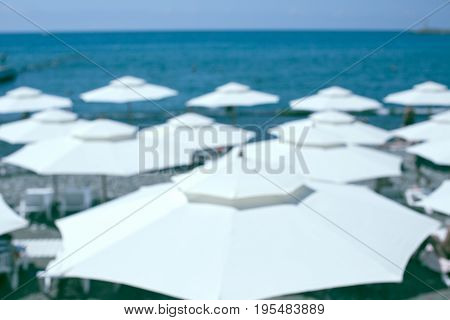 White beach umbrellas against blue sea and sky. Summer vacation concept. Exotic travel destination. Shot deliberately out of focus to serve as background. Horizontal