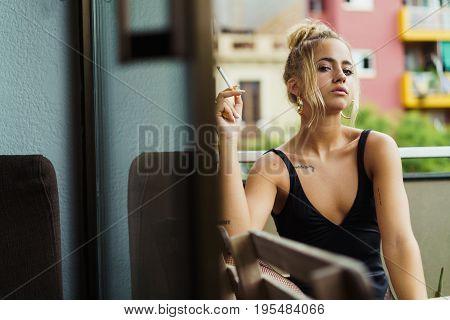 Confident Woman Smoking On Balcony