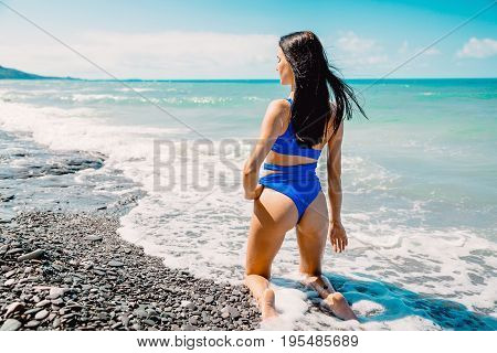 Beautiful woman in swimwear standing up on the beach, wearing stylish bikini