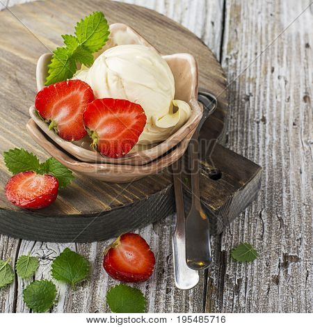 Homemade cream ice cream from organic cow cream in a vintage ceramic vase with fresh strawberries and melissa in rustic style. Selective focus