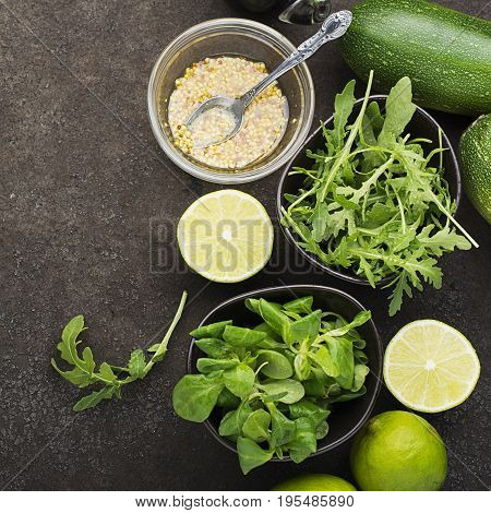 Ingredients for salad: rucola, root salad, olive oil, limes on a dark background. Seasonal Healthy Eating