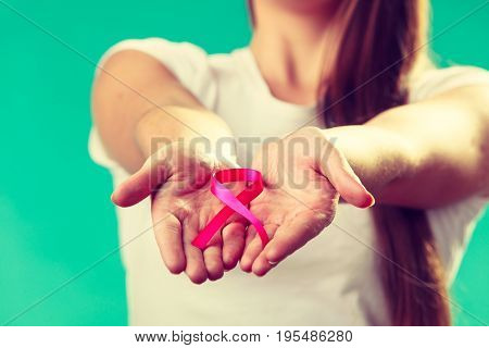 Woman With Breast Cancer Awareness Ribbon On Hands