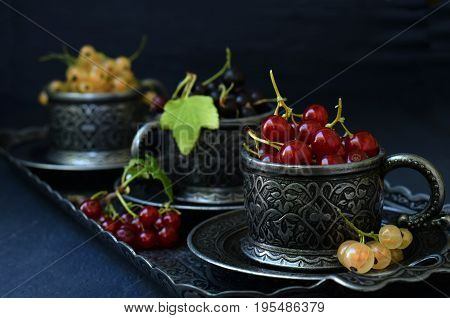 Composition Of Fresh Ripe Berries: Red, Black And White Currants On A Dark Gray Concrete Background.