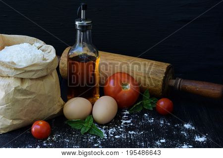 Composition Of Bag Of Wheat Flour, Eggs, Oil, Tomato And Rolling Pin. Preparation For Kneading Dough