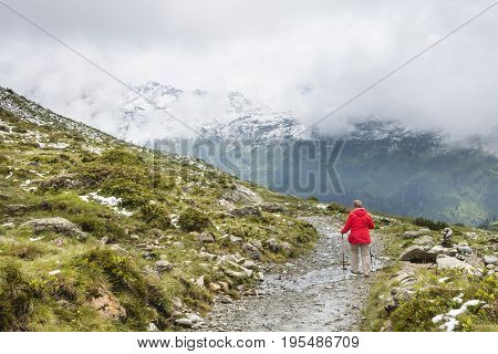 A female senior hiker wearing a red coat hiking in the Paznaun Valley near Galtur in Austria.