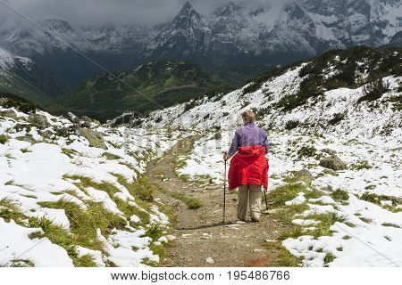 A female senior hiker wearing a red coat hiking through snow in summer on the way to the Zeinisjoch in the Paznaun Valley near Galtur in Austria.