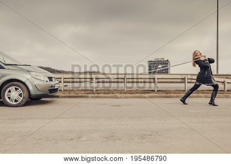 Woman Pulling Broken Car On Road