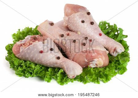 Three raw chicken drumsticks with lettuce leaf isolated on white background.