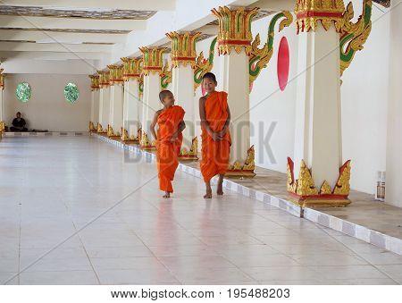 Sangkhlaburi Thailand- March 05 2017: Two Buddhist novice monks walking along the corridor of the temple in Sangkhlaburi District Kanchanaburi Province Thailand.