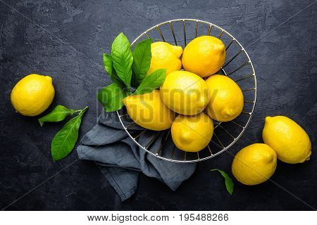 Fresh lemons with leaves on dark background, top view